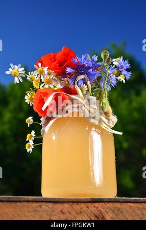 Glas voll mit leckeren frischen Honig und Wiesenblumen im Bienenstand gegen blauen Himmel - Stockfoto