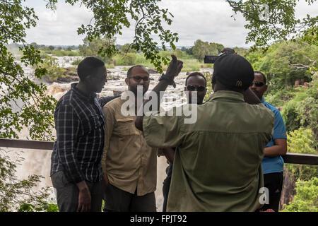 Afrikanische Touristen mit ihrem Foto im Mosi-Oa-Tunya Nationalpark (Victoria Falls), Livingstone, Sambia, Afrika - Stockfoto
