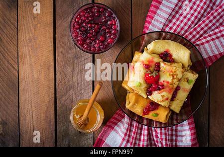Goldene Pfannkuchen mit Preiselbeermarmelade und Honig im rustikalen Stil. Ansicht von oben - Stockfoto