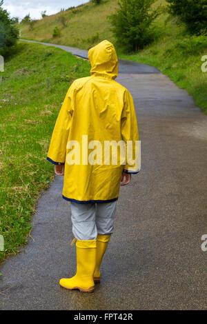 Junge Frau trägt einen gelben Regenmantel und Kautschuk Stiefel Wandern in der Natur - Stockfoto
