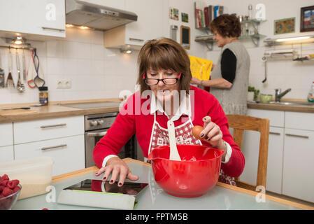 Ältere Frau sucht Rezept auf digital-Tablette für Kuchen, München, Bayern, Deutschland - Stockfoto