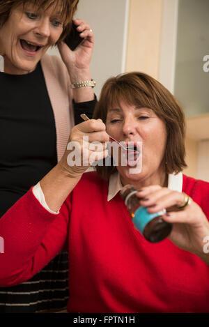 Ältere Frau schlucken flüssige Medizin und ihre Freundin sprechen auf Smartphone, München, Bayern, Deutschland
