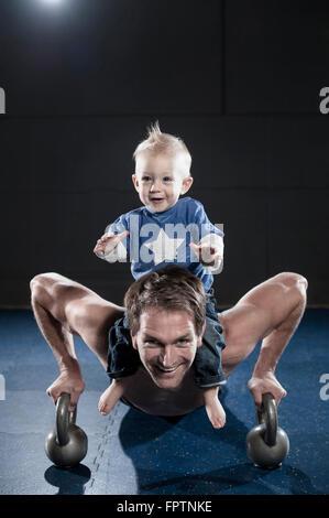 Porträt von lächelnden Sportler tun Push Ups tragen Sohn auf Schulter, Bayern, Deutschland - Stockfoto
