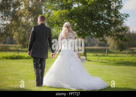 Rückansicht des ein Brautpaar zu Fuß auf dem Rasen, Ammersee, Upper Bavaria, Bavaria, Germany - Stockfoto