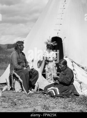 1920ER JAHREN INDIANISCHE INDISCHE FAMILIE MANN FRAU KIND VON TIPI STONEY SIOUX STAMM IN DER NÄHE VON ALBERTA, KANADA - Stockfoto