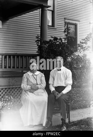 1900ER JAHRE PORTRAIT PAAR MANN FRAU SITZEN AUF STÜHLEN VOR HAUS BLICK IN DIE KAMERA - Stockfoto