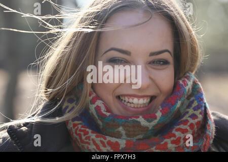 Nahaufnahme eines Mädchens Augen wie sie lächelt, ihr Haar weht im Wind - Stockfoto