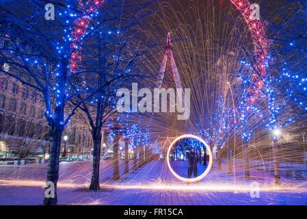 Silhouette des Menschen Spinnen beleuchtet Stahlwolle in der Nacht in der Nähe von London Eye Southbank in London, - Stockfoto
