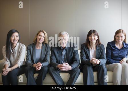 Porträt, Lächeln Geschäftsleute in Folge auf sofa - Stockfoto