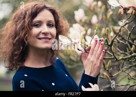 Ein Modell, Blumen in einem Park zu genießen. - Stockfoto