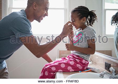 Papa kneifen jungen Töchter Nase - Stockfoto