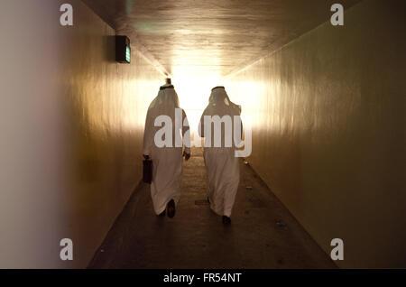 Zwei saudische Männer gehen in einem Tunnel. - Stockfoto
