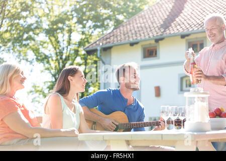 Vater Eröffnung Flasche Roséwein für Familie an sonnigen Patio Tisch - Stockfoto