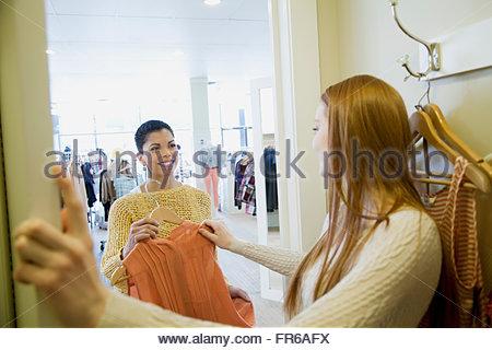 hübsche junge Frau, die versucht auf Kleidung - Stockfoto