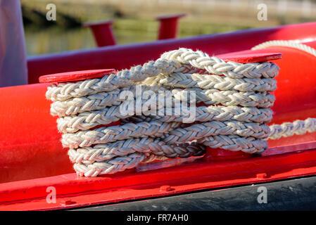 Festmacher Seil verdreht auf einem roten Schiff. Seil ist weiß, aber ein bisschen schmutzig und gut genutzt. - Stockfoto