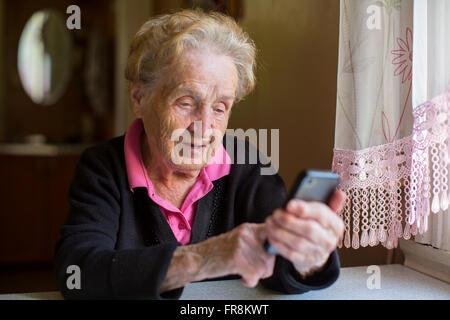 Ältere Frau am Tisch auf einem Smartphone eingeben. - Stockfoto