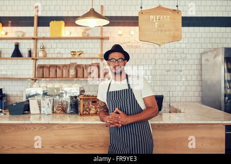 Porträt einer zuversichtlich junge Kaffee-Shop-Betreiber stehen an der Theke Café. Hübscher junger Mann arbeitet - Stockfoto