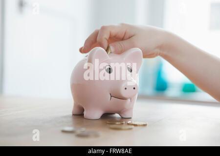 Kleiner Junge, Münze ins Sparschwein, Nahaufnahme - Stockfoto