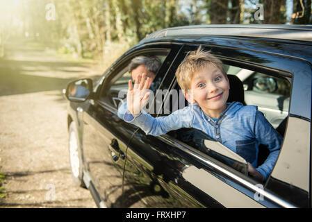 Eine zehn Jahre alte Blondschopf winkt seine Hand durch das Autofenster. Er schaut in die Kamera, trägt ein blaues - Stockfoto