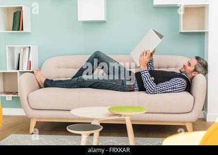 Ein Mann in seinen Vierzigern liegt barfuß, mit seinem Laptop über ihm wie ein Buch öffnen, auf einem Sofa in einem - Stockfoto