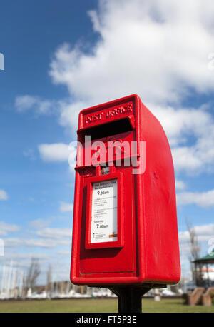 Einen roten Briefkasten vor einem blauen bewölkten Himmel abgebildet - Stockfoto