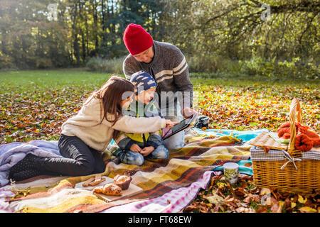 Vater und Kinder mit digital-Tablette auf der Picknickdecke im Wald - Stockfoto