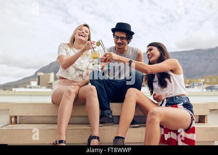 Glückliche junge Freunde sitzen auf Stufen und Toasten Cocktails. Junge Menschen mit einer Party auf dem Dach. Mann und Frau hängen outd