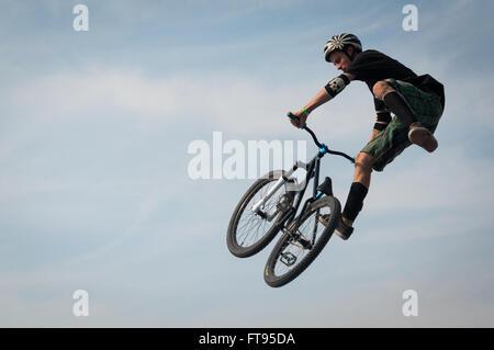 Biker mit BMX Fahrrad in die Luft springen, Dirt Jumping - Stockfoto