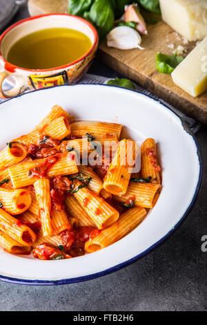 Nudeln. Italienische und mediterrane Küche. Pasta Rigatoni mit Tomaten-Sauce Basilikum Blätter Knoblauch und Parmesan - Stockfoto