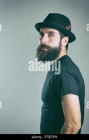 Seitenansicht des harten bärtiger macho Mann trug schwarze T-shirt und Hut Blick in die Kamera. Retro-getönten gefilterte - Stockfoto