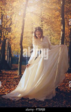 Schöne Frau mit viktorianischen Kleid im herbstlichen Wälder. Abendlicht - Stockfoto