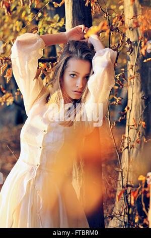 Schöne junge Frau posiert im warmen Abendlicht. Herbstfarben Stockfoto