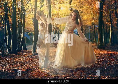 Schöne Frau tanzt im herbstlichen Wälder. Surreal und romantisch Stockfoto
