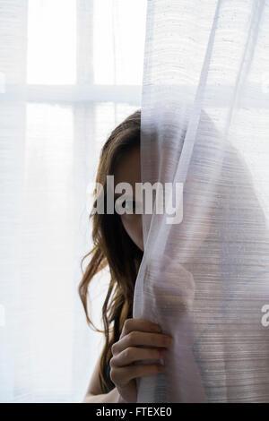 Ernste junge Frau versteckt sich hinter die Vorhänge am Fenster - Stockfoto