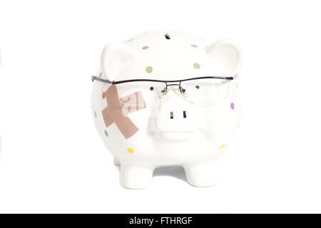 Bandagierte Sparschwein mit Brille isoliert auf weiss - Stockfoto