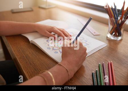 Schließen Sie herauf Bild der Frau Hände zeichnen in Erwachsene Malbuch auf einem Tisch zu Hause. - Stockfoto