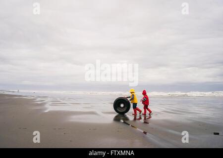 Zwei jungen, die einen verlassenen Reifen aus dem Meer an den Strand Rollen - Stockfoto