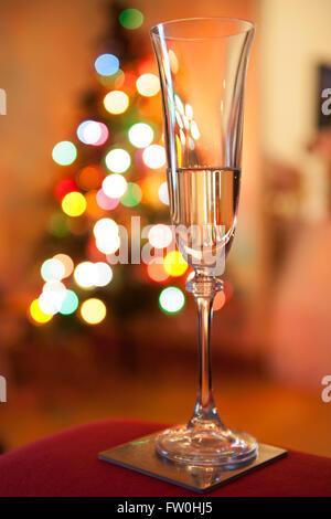 Einem prickelnden Glas Champagner mit Luftblasen vor unscharfen Weihnachtsbaums - Stockfoto