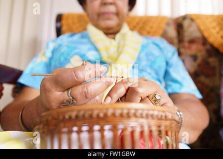 Alte Menschen in geriatrischen Hospiz: Senior Frau sitzt auf dem Sofa im Krankenhaus, stricken mit Wollknäuel. Die - Stockfoto