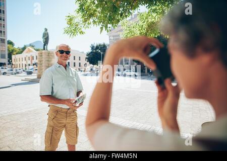 Senior woman für Fotos zu posieren. Mann von seiner Frau im Urlaub fotografiert. - Stockfoto