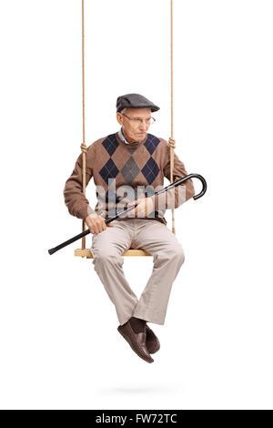 Vertikale Aufnahme eines depressiven senior Mannes auf der Suche nach unten sitzen auf einer Holzschaukel isoliert - Stockfoto