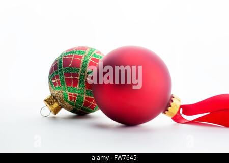 Eine rote und eine karierte Glas christmas Ornament mit roter Schleife auf weißem Hintergrund. - Stockfoto
