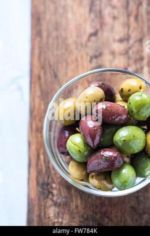 Frische ganze Oliven in Schüssel geben, mit Öl und Gewürzen. Spanische Tapas-Konzept. - Stockfoto