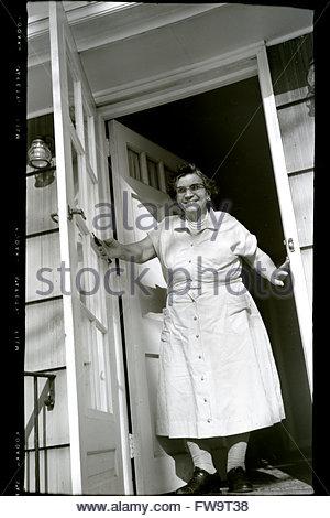 1960er jahren l chelnd senior senioren alte dame oma oma sitzt im schaukelstuhl blick auf kamera. Black Bedroom Furniture Sets. Home Design Ideas
