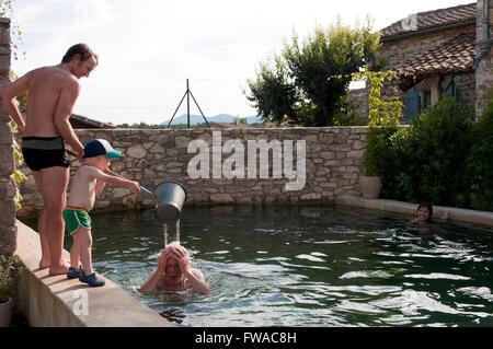 Vater und Sohn einen Eimer Wasser über Opas Kopf gießen - Stockfoto