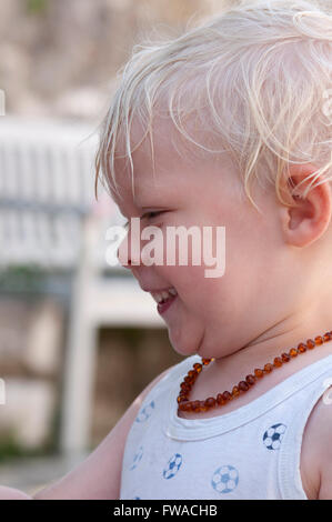 Profil eines glücklich lächelnden Kleinkindes mit blondem Haar und trägt eine Halskette - Stockfoto