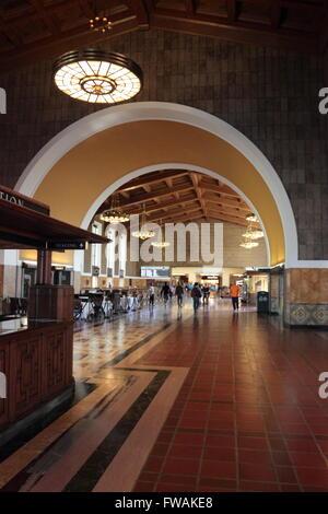Innere der Union Station, Los Angeles, Kalifornien, USA zeigt den Informationsstand und Pendler Fräsen in der Ferne. - Stockfoto