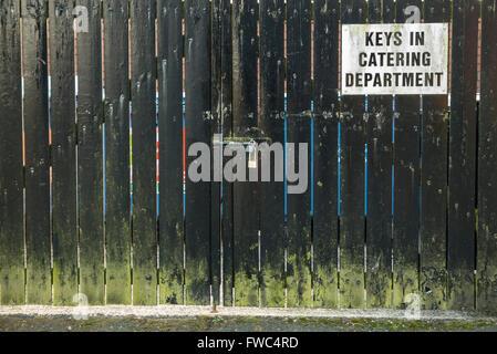 Schild an einem verschlossenen Holztor rät, dass der Schlüssel von der catering-Abteilung zur Verfügung.