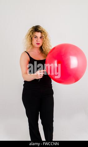 Einzelne Erwachsenfrau Sprengung ein Medium sized roten Ballon