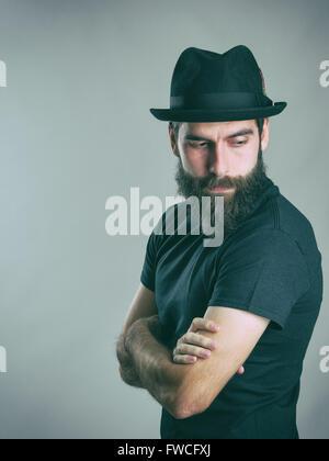 Seitenansicht des traurigen bärtige stilvollen Mann mit Hut zurück über die Schulter schauen. Retro-Stil getönten - Stockfoto